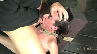 The BDSM master fucks Hailey Young in the mouth while her head is fixed to the post